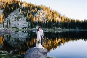 Louie Lake is an adventurous wedding venue in McCall Idaho. Couple standing on rock with mountain reflecting on lake water.