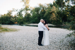 Elopement couple stands together on the Boise River in Eagle, Idaho.